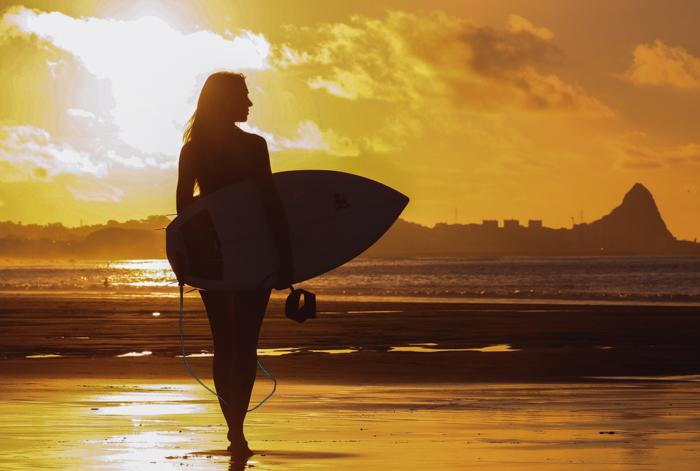 A silhueta de uma mulher segurando uma prancha de surfe na praia iluminada pelo sol poente
