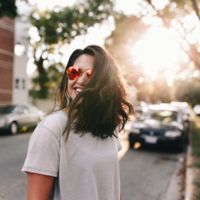 Uma imagem de uma mulher usando óculos escuros em uma rua da cidade iluminada pelo sol poente