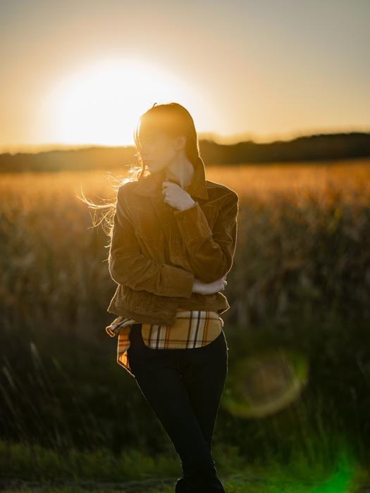 Imagem de uma mulher posando em um prado com o sol poente atrás dela