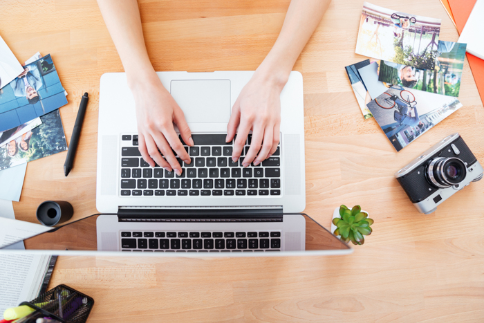 Top view of desktop of young woman photographer working with a macbook
