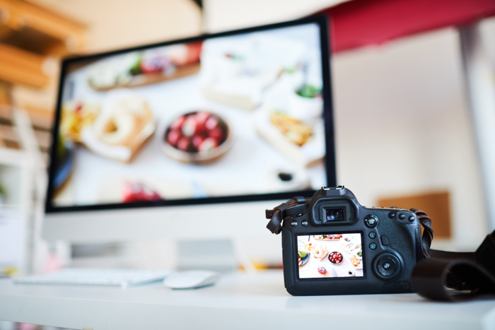 Background image of photo camera with photo of food on table against computer with editing software