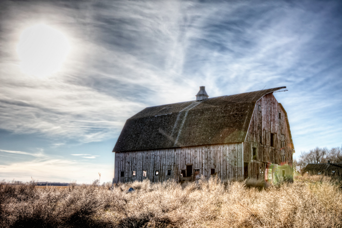 an hdr image of an abandoned barn and winter sky