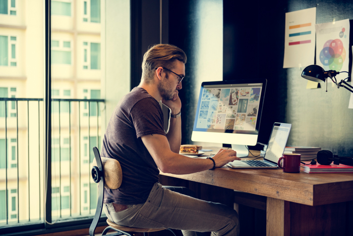 an image of a man in glasses working at a desk with desktop and laptop