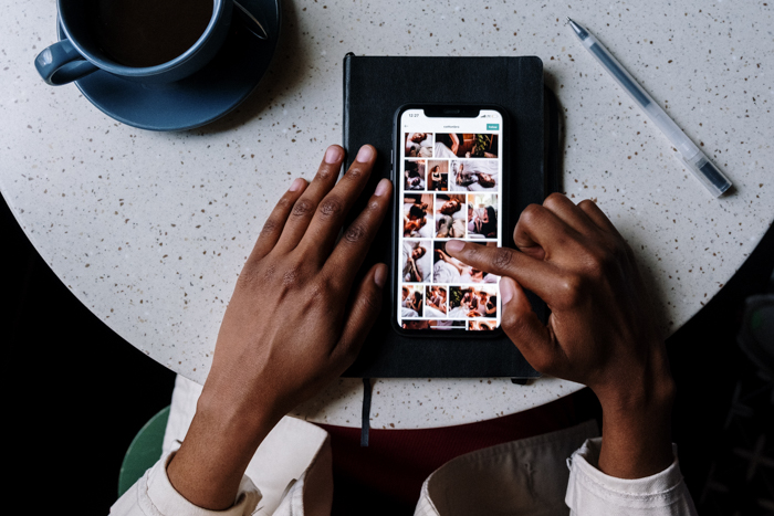 an overhead image of tow hands scrolling through a smartphones photos