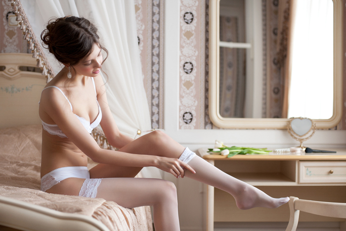 Boudoir photo of a bride, dressing before the big day.