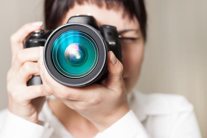 Close-up de uma mulher segurando uma câmera e fotografando com ela.