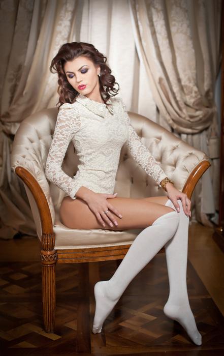 Fotografia de boudoir de uma mulher posando em uma cadeira com um corpete de renda e meias brancas até o joelho.