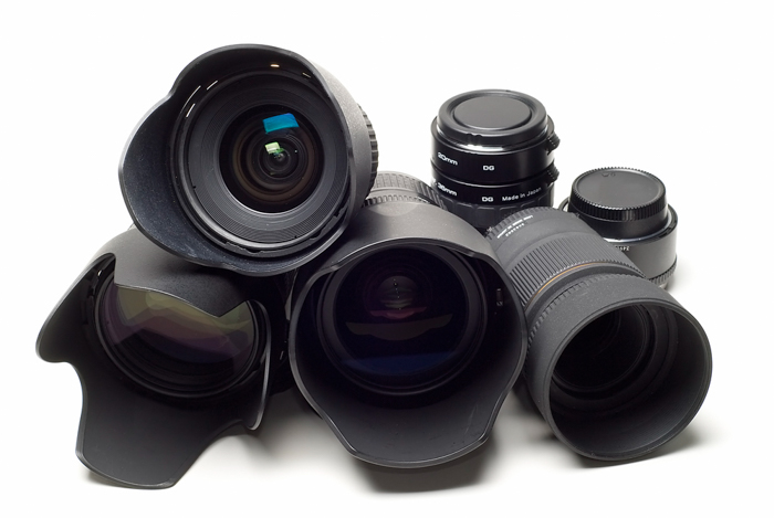 A pile of camera lenses on white background.