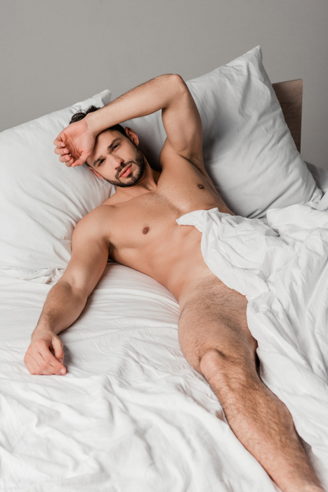 Naked man laying in a bed among white sheets.