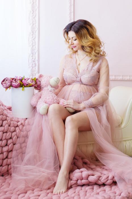 Maternity boudoir portrait of a girl in pink lingerie