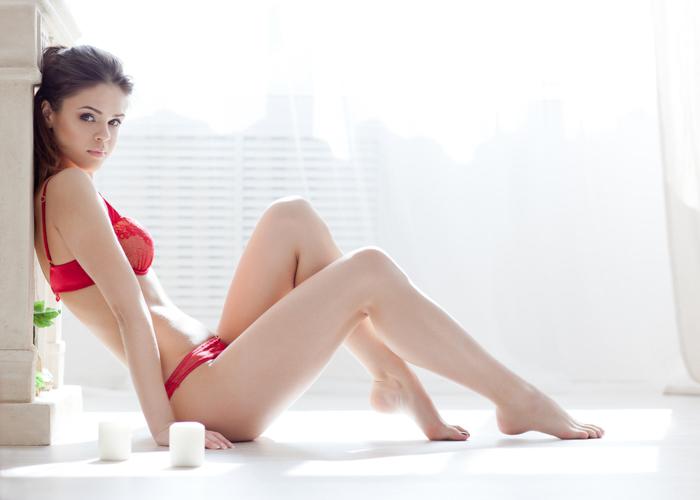 Imagem de boudoir de uma mulher sentada em uma janela, vestida com lingerie vermelha.