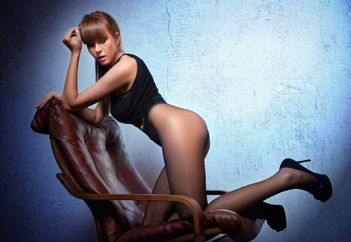 Boudoir photo of a woman posing on a chair, wearing lingerie and high heels.