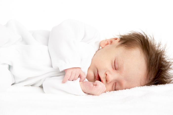 Bayi Tidur miring di atas selimut