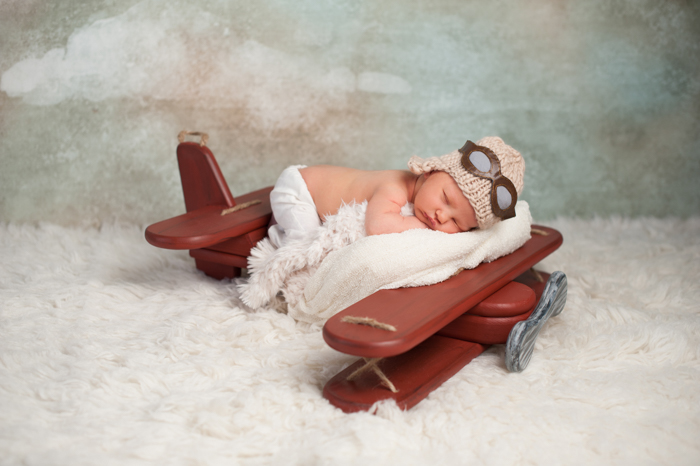 bayi berpose di atas penyangga pesawat yang menarik