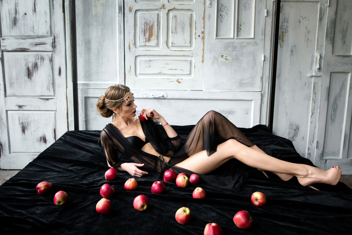 a boudoir photo of a woman posing on a black bed with red apples