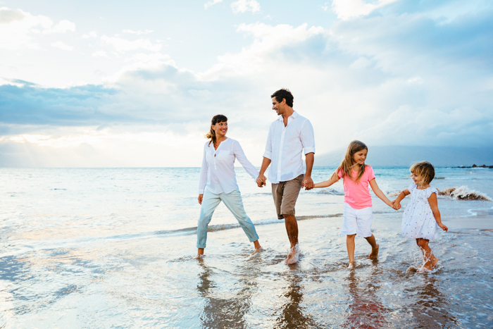 a family of four walks across the beach with their feet in the shallow water