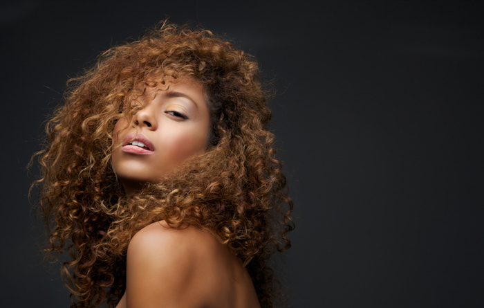 a curly haired model poses over the shoulder