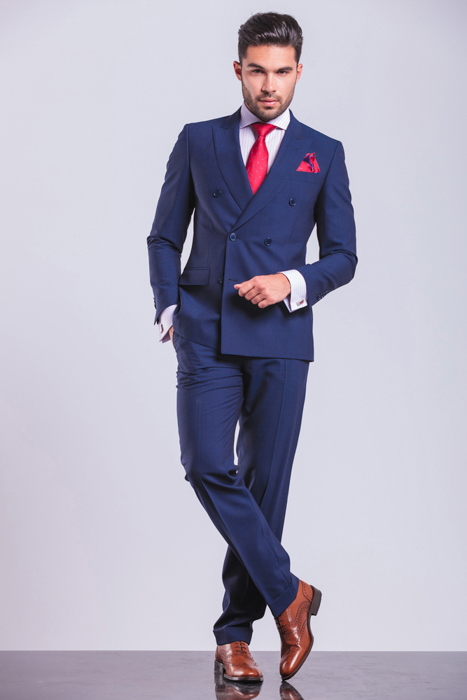 a male poses in blue suit and red tie posing