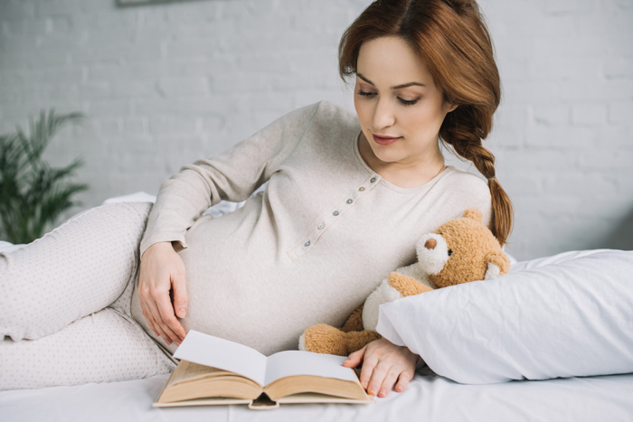 a pregnant woman poses on her side while reading a book and holding a teddy bear