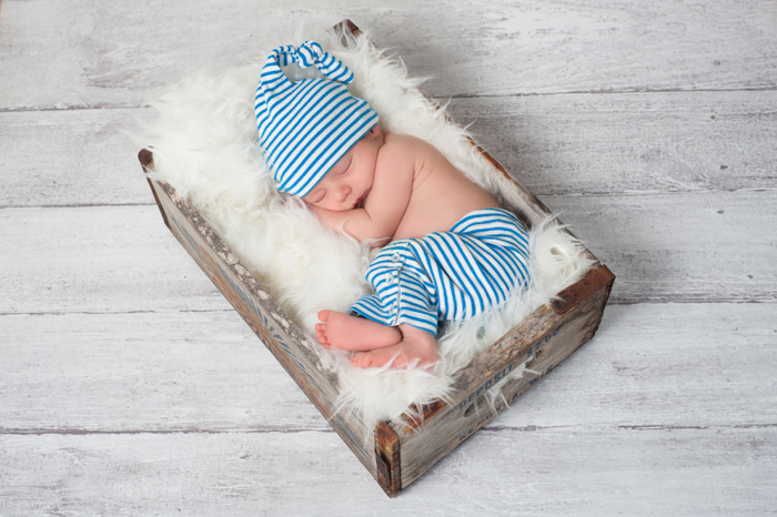 a top down shot of a newborn sleeping in a wood and feather box