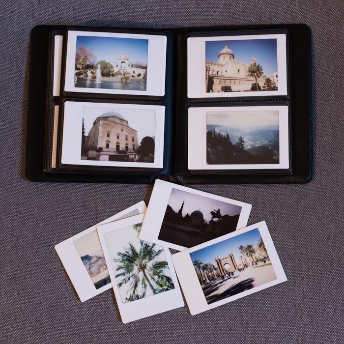 uma foto aérea de um álbum de fotos fujifilm instax mini 8 com fotos instantâneas impressas na parte interna e externa
