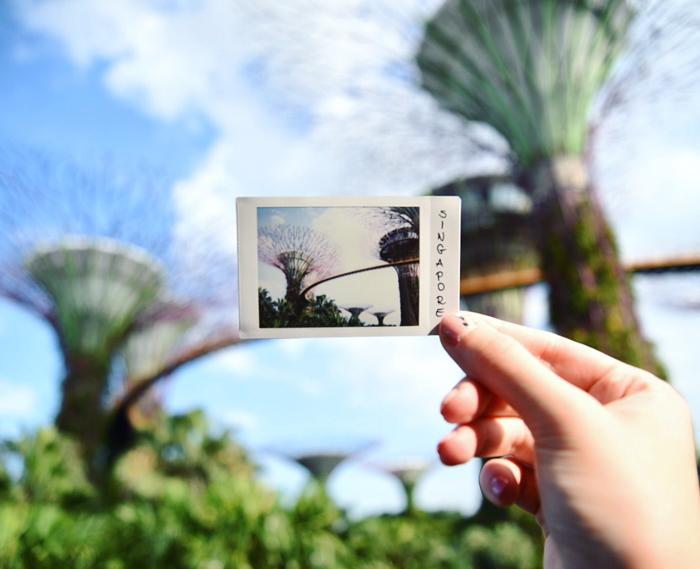 uma imagem de uma mão segurando um exemplo de uma foto de fujifilm instax mini 8 de Singapura