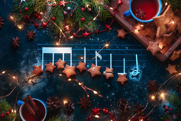 As notas da melodia de Natal são planificadas com biscoitos em forma de estrela, ramos de abeto, bandeja de madeira, estrelas de anis e decorações.