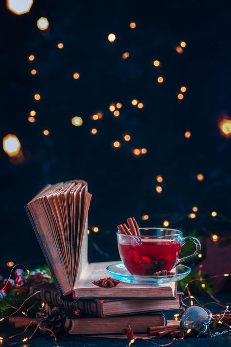 Chá de frutas vermelhas em uma pilha de livros com luzes coloridas. Bebida de Natal em um fundo escuro com espaço de cópia