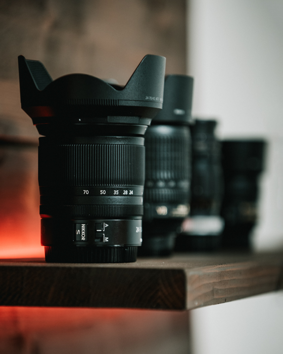 Different camera lenses on a shelf