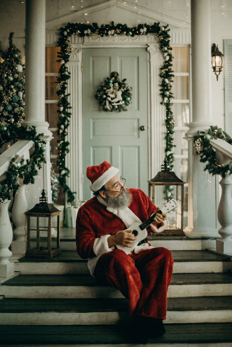 Funny Christmas card photo idea of santa Claus playing the ukulele