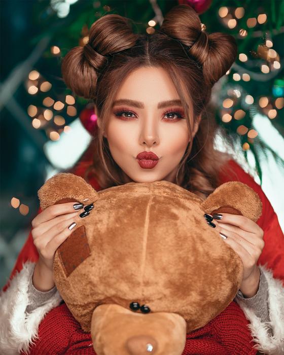 ndoor retrato de Natal de uma modelo feminina posando em frente à árvore de Natal