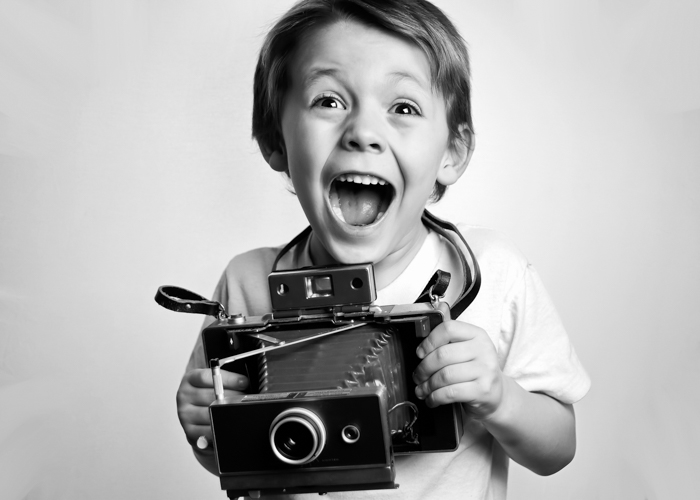 A little boy holding a vintage camera