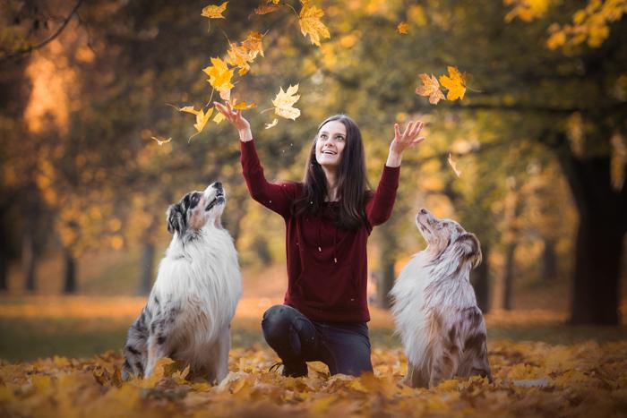 Fotografia de uma mulher brincando com dois cachorros ao ar livre
