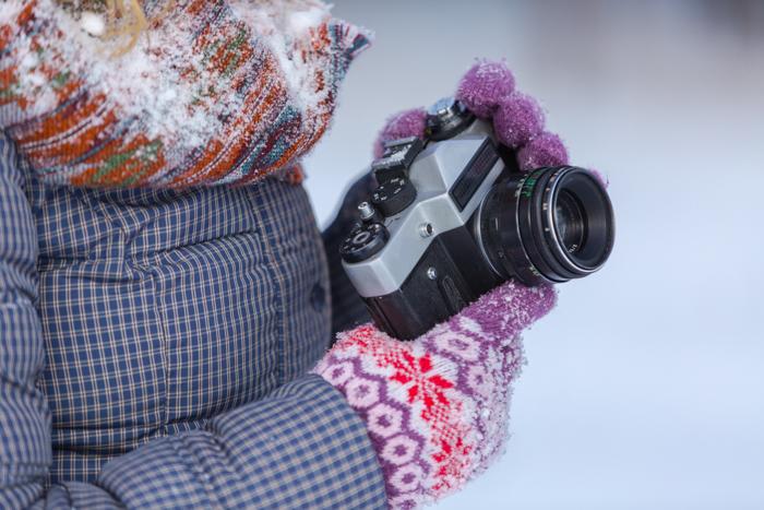 Close de um fotógrafo tirando fotos da neve