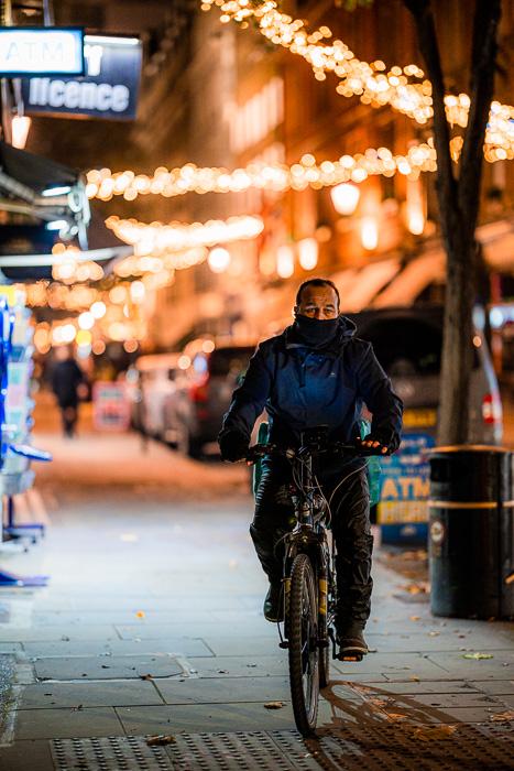 Fotografia de rua de um ciclista na rua tirada com a Canon RF 85mm