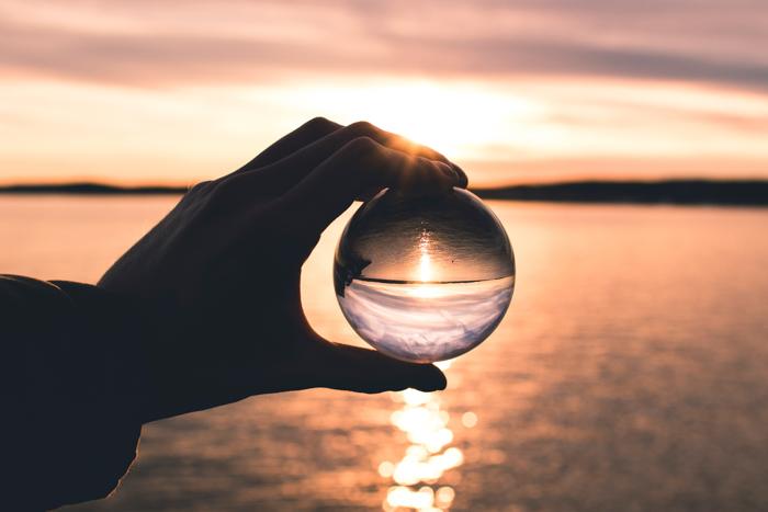 Uma pessoa segurando uma bola de cristal em frente a uma paisagem marinha.