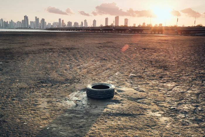 Uma imagem documental de um pneu de borracha em um terreno árido contra um horizonte urbano