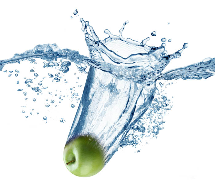 A maçã verde cai profundamente na água com um grande respingo.