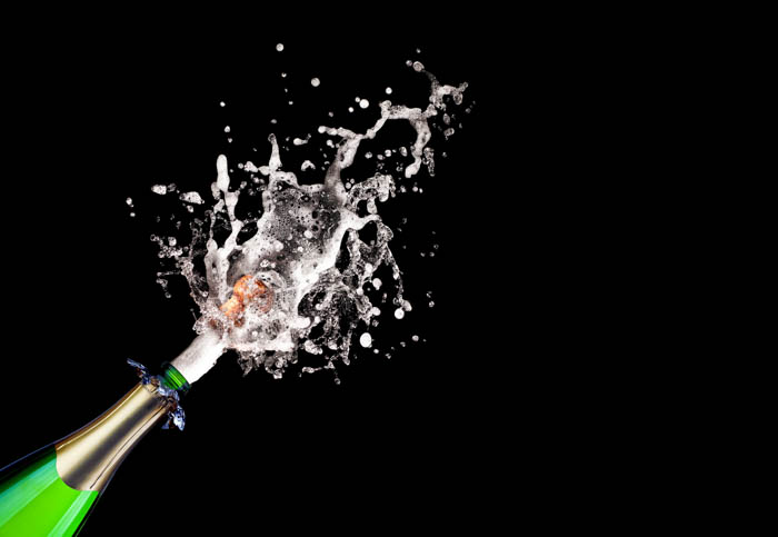 Estourando champanhe em fundo preto