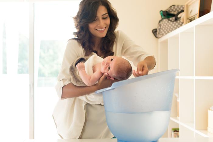 Ideia fofa da foto do recém-nascido da mãe dando banho no bebê