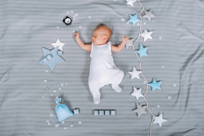 Ideia de fotografia aérea de um bebê recém-nascido descansando em uma cama ao lado de acessórios e brinquedos