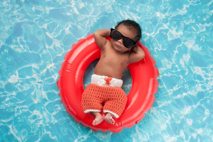 Ideia divertida da fotografia de um recém-nascido de um bebê empoleirado em óculos de sol em um anel de borracha em uma piscina