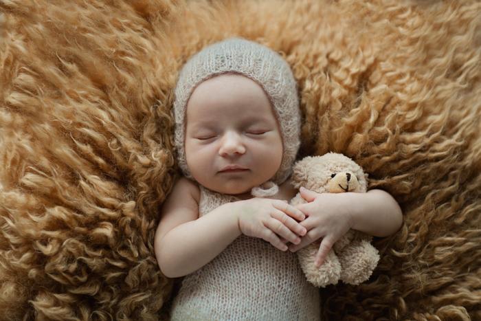 Doce retrato de um bebê recém-nascido segurando um ursinho de pelúcia