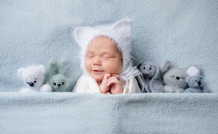 Sweet portrait of a newborn baby in bead with teddy bears
