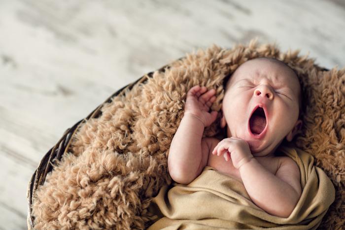 Doce retrato de um bebê recém-nascido bocejando