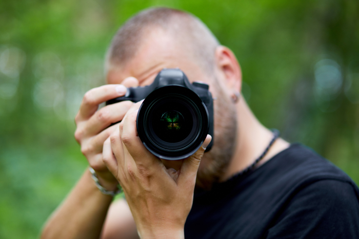 A man taking a photo outdoors with a DSLR