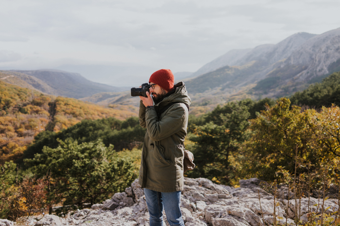 A man in a photographer jacket taking a photo outdoors with a DSLR