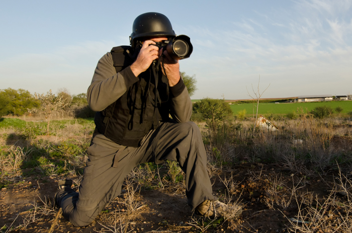 A man in a photographer vest taking a photo outdoors with a DSLR