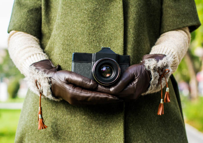 Winter photography gloves with firm grip holding a camera
