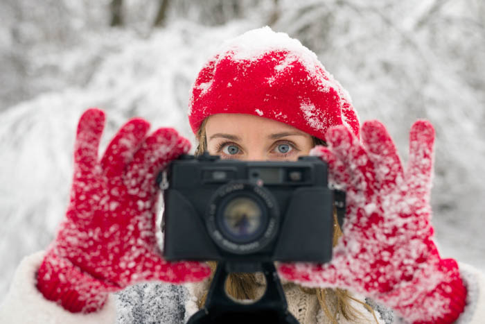 Girl holding a camera in her hands while wearing photography gloves